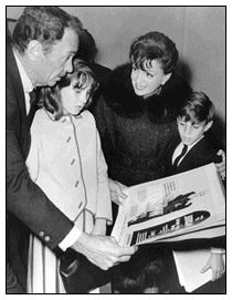 "Judy Garland with Barry Sullivan, Lorna Luft and Joe Luft looking at the poster planned to prmote Judy's involvement in ""Harlow"""